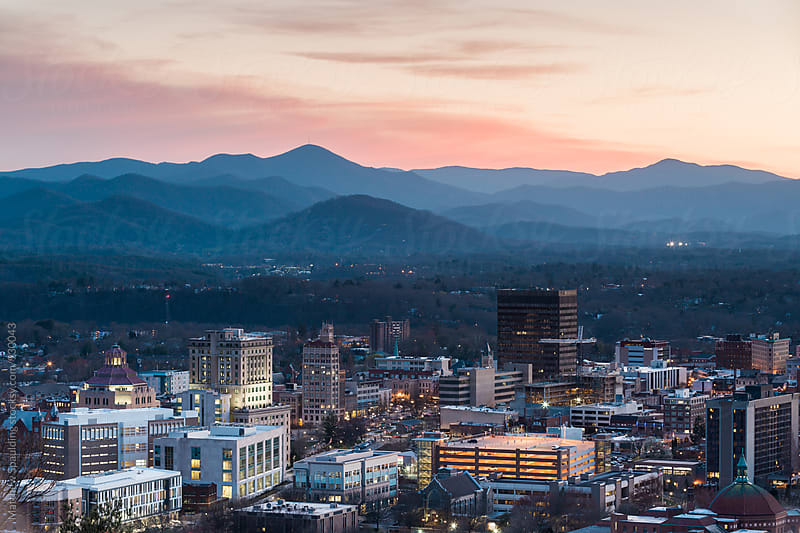 View of Asheville city skyline and mountains after sunset by Matthew Spaulding for Stocksy United