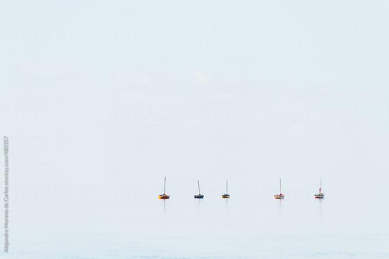 Aligned sailboats on calm sea by Alejandro Moreno de Carlos for Stocksy United