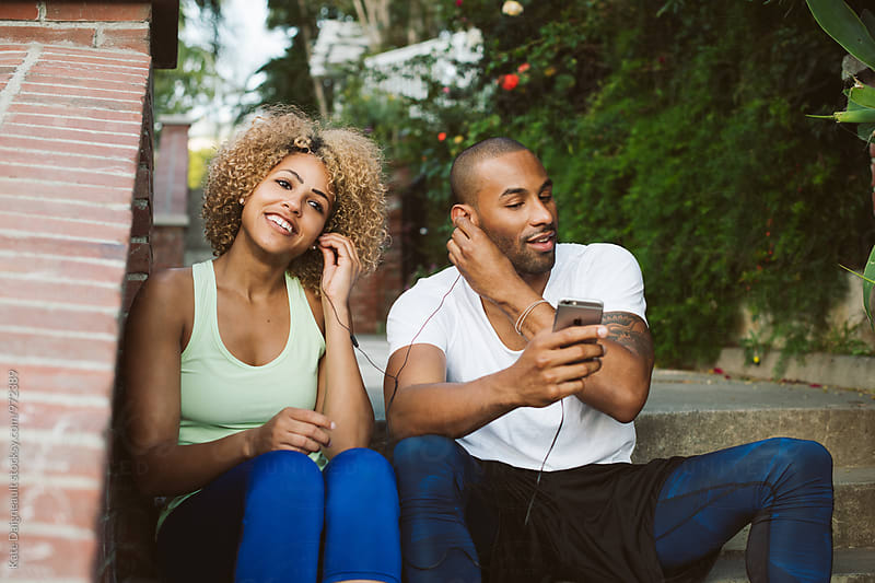 Cute African American couple listening to music after working out together. by Kate Daigneault for Stocksy United