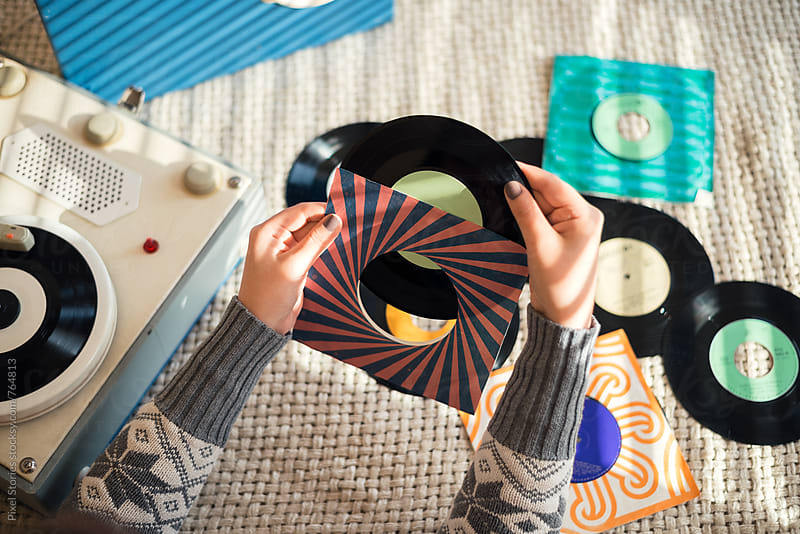 Young woman getting vinyl record out of its sleeve by Pixel Stories for Stocksy United