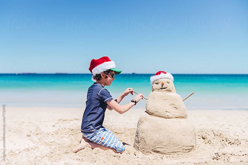 Boy making a sand snowman at the beach on Christmas day in Australia by Angela Lumsden for Stocksy United