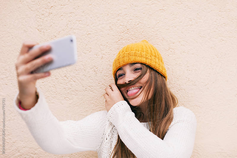 Happy teen girl taking a selfie with her smartphone outside. by BONNINSTUDIO for Stocksy United