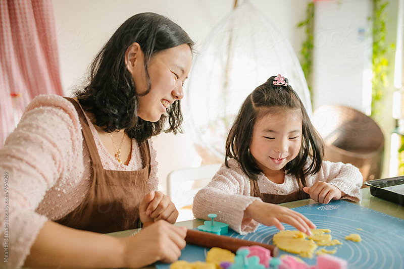Young mother and daughter baking biscuits by MaaHoo Studio for Stocksy United
