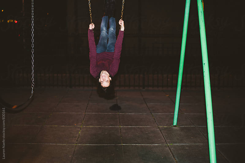 Young woman on the swings at night by Lauren Naefe for Stocksy United