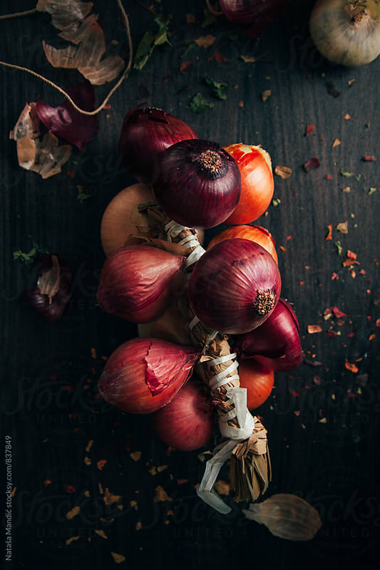 Onions on wooden table by Nataša Mandić for Stocksy United