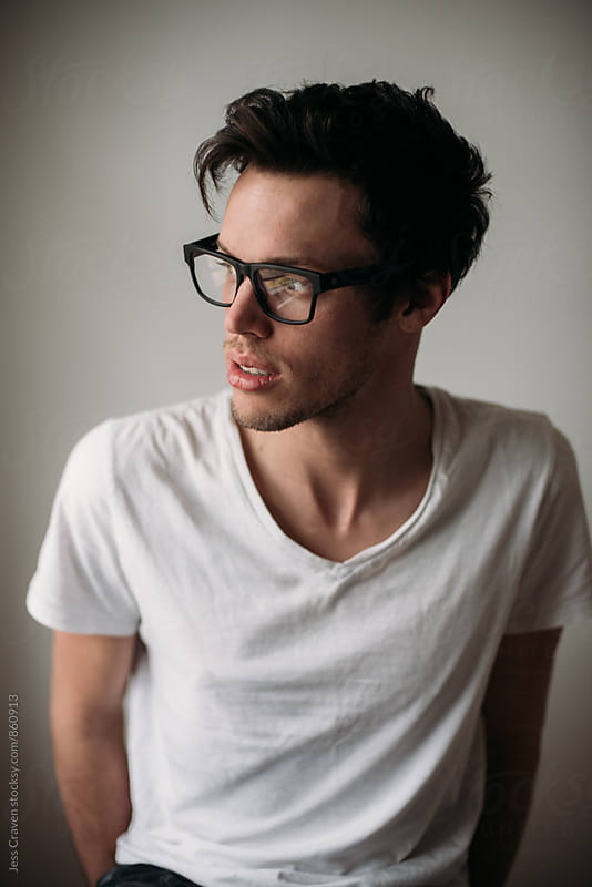 Male wearing dark frame glasses and white t-shirt by Daring Wanderer for Stocksy United