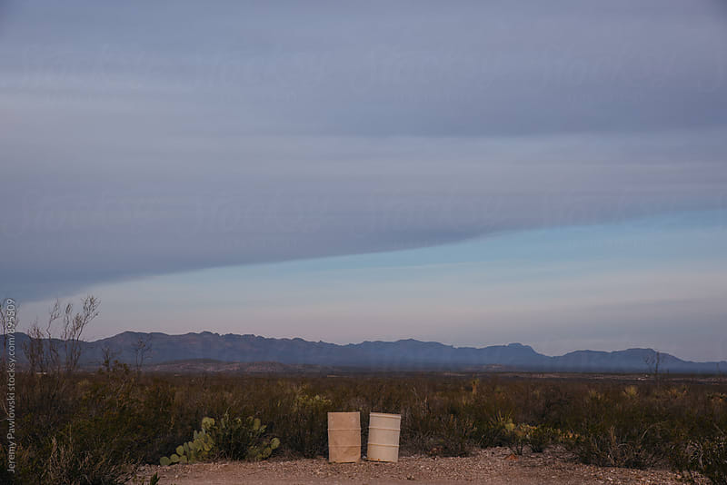 Two trash barrels on dirt road in the desert by Jeremy Pawlowski for Stocksy United