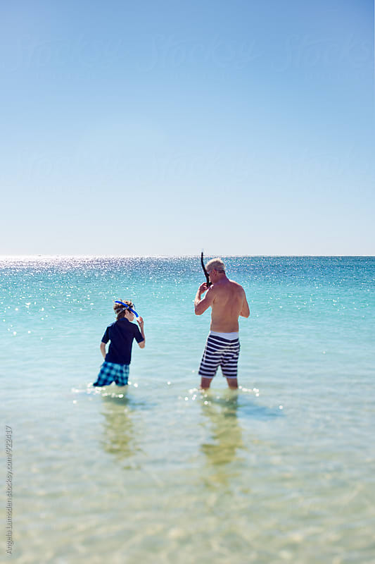 Father and son with snorkels standing together in clear water at the beach by Angela Lumsden for Stocksy United