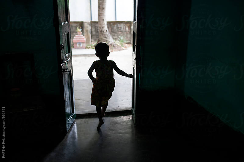 A little girl exiting through a door by PARTHA PAL for Stocksy United