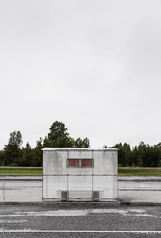 Lonely and empty bus stop on a cloudy day by Melanie Kintz for Stocksy United