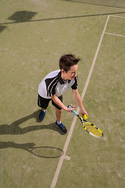 High angle view of young male serving a tennis ball by Ben Ryan for Stocksy United