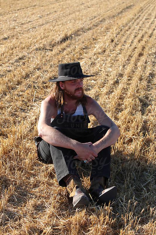 Cowboy Sitting Down In A field by Carey Haider for Stocksy United