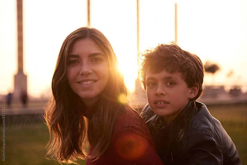Sister and brother smiling at camera  by Guille Faingold for Stocksy United