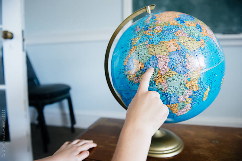 Hands of a child point to Africa on a classroom globe by Cara Dolan for Stocksy United