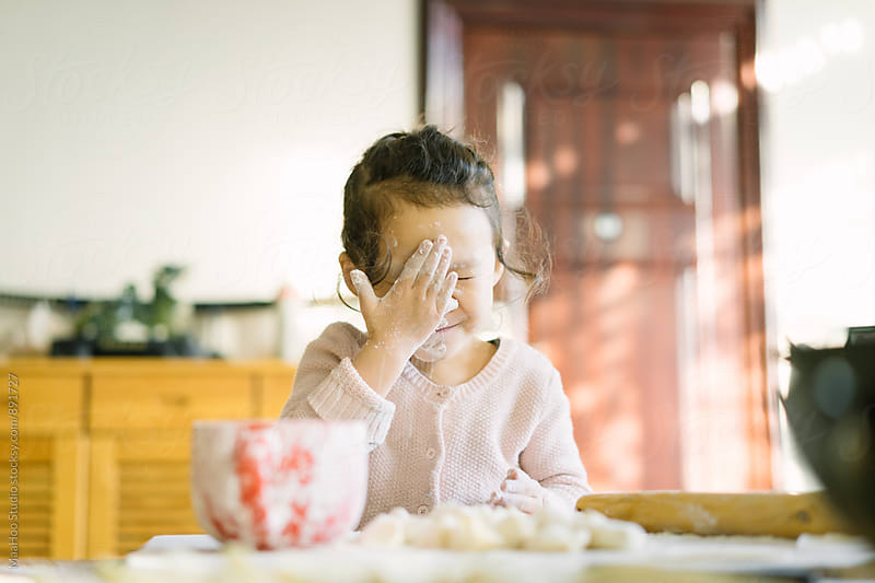 Toddler girl making dumplings and putting flour on her face by MaaHoo Studio for Stocksy United