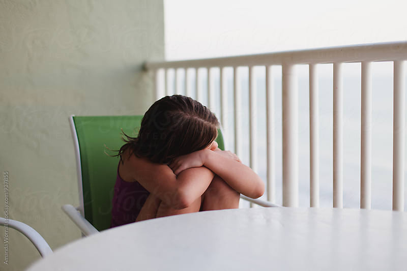 Girl watching sunset over balcony on vacation by Amanda Worrall for Stocksy United