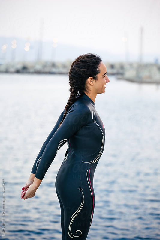 Side view of a woman wearing a wetsuit doing stretching exercise. by BONNINSTUDIO for Stocksy United