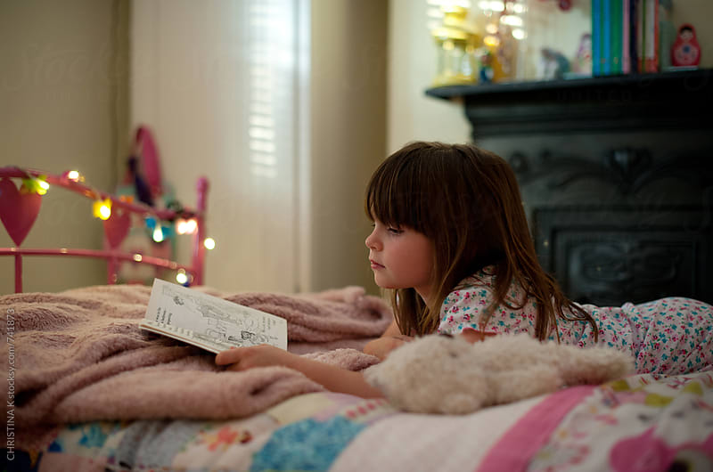 Girl laying on her bed reading by Christina Kilgour for Stocksy United
