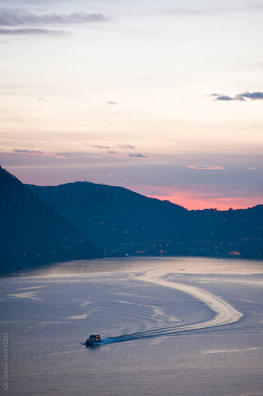 Boat in Lake Como at sunset by Simone Becchetti for Stocksy United