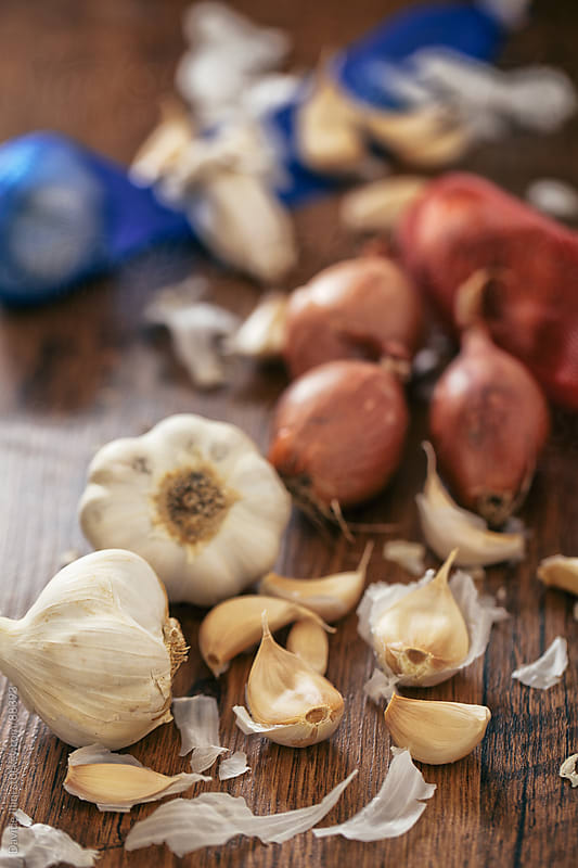 Cloves of garlic and onions on a Table. by Davide Illini for Stocksy United