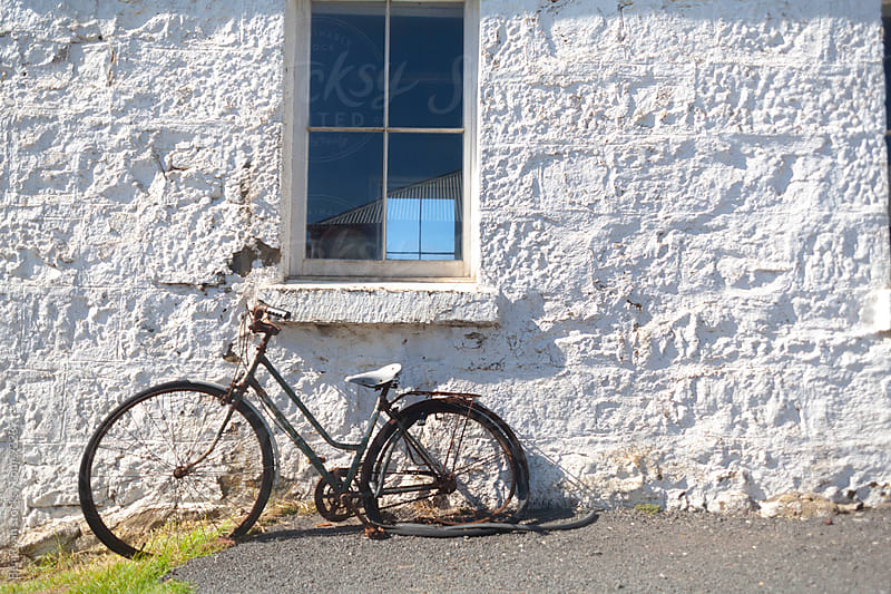 Rusted bicycle against white stone wall by Ben Ryan for Stocksy United