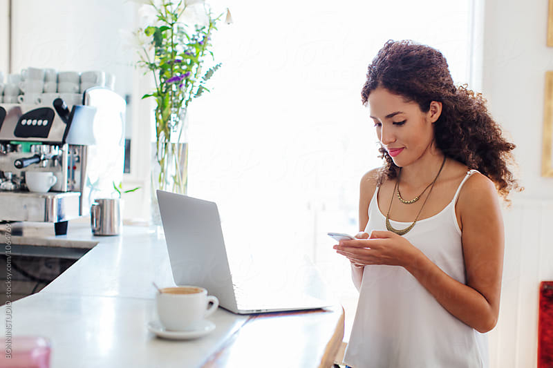 Young businesswoman using her phone working in a coffee bar.  by BONNINSTUDIO for Stocksy United