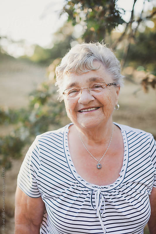 Elderly woman smiling in the sunshine by Rob and Julia Campbell for Stocksy United