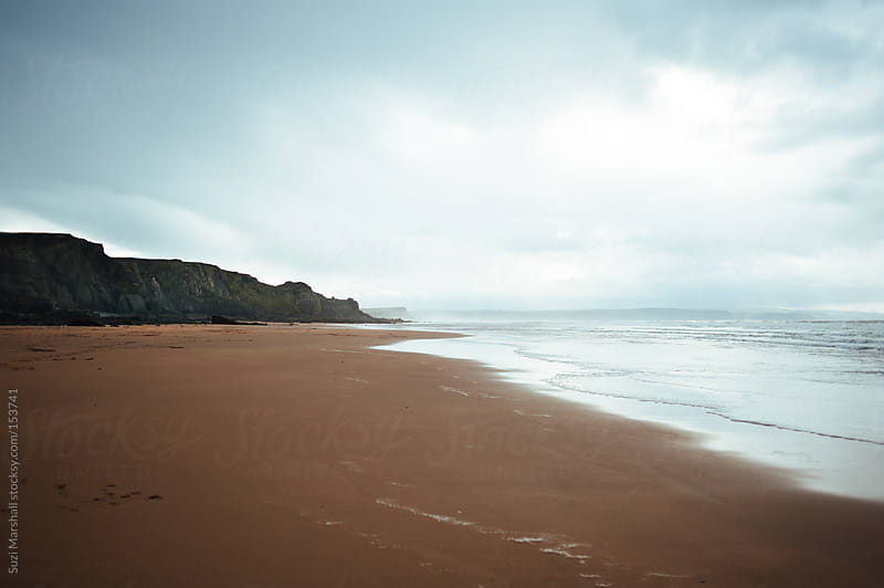 Beach and cliffs on a stormy day by Suzi Marshall for Stocksy United