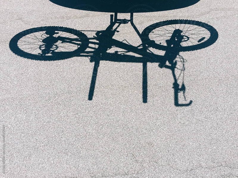 Shadow on road of bike on bicycle carrier by Jacqui Miller for Stocksy United