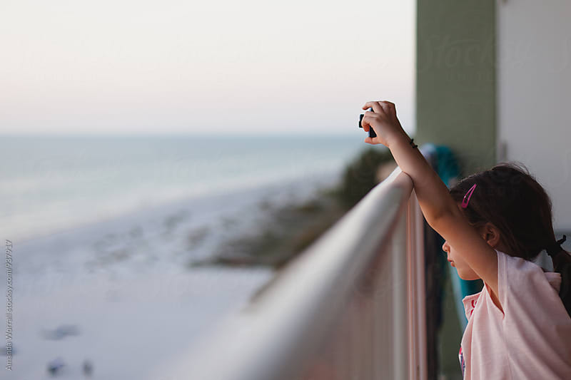 Child taking a photo while watching the sunset at the beach by Amanda Worrall for Stocksy United