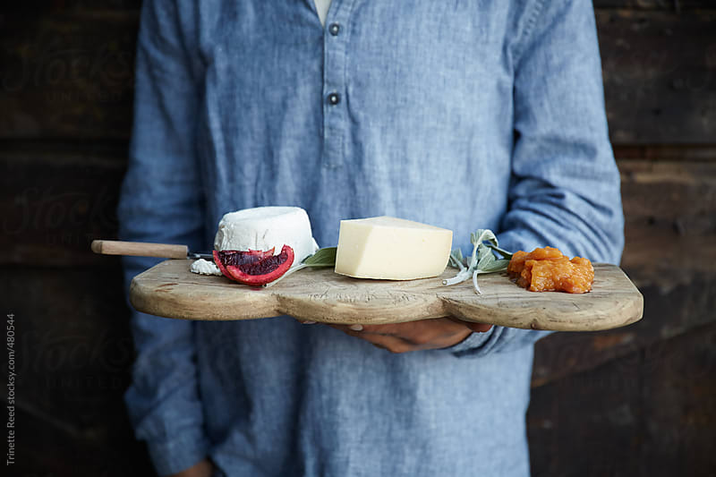 Man holding rustic cheese plate inside a barn by Trinette Reed for Stocksy United
