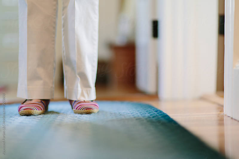 Senior Woman in Hallway of Home with Cozy slippers by Raymond Forbes LLC for Stocksy United