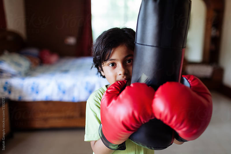 Child wearing boxing gloves holds the punch bag by Saptak Ganguly for Stocksy United