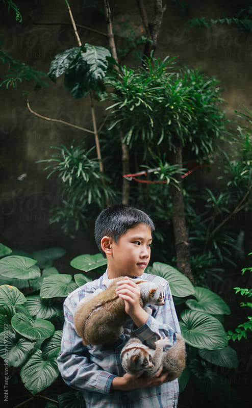 Boy portrait with 2 monkeys by Nabi Tang for Stocksy United
