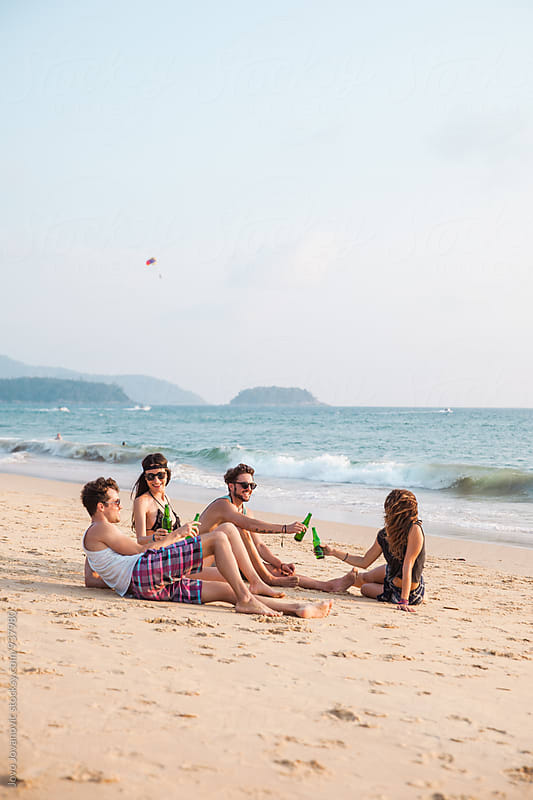 Group of four friends enjoying cold drinks at the beach by Jovo Jovanovic for Stocksy United