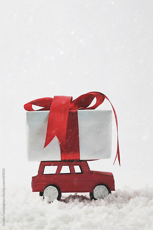 Red ribbon gift on toy car in snow by Sandra Cunningham for Stocksy United
