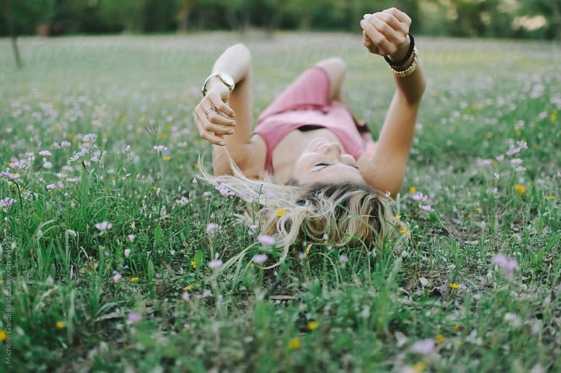 Young woman in wildflower field  by Michelle Gardella for Stocksy United