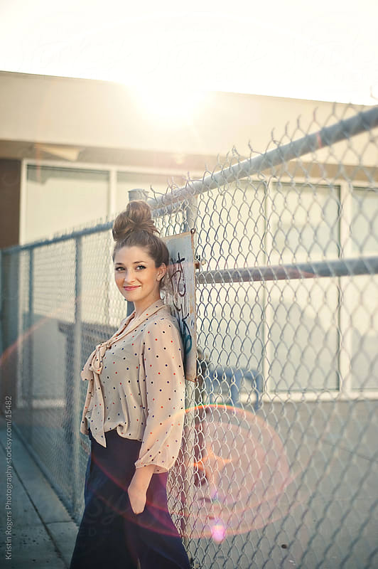 fashionable young lady leaning on fence in alley by Kristin Rogers Photography for Stocksy United