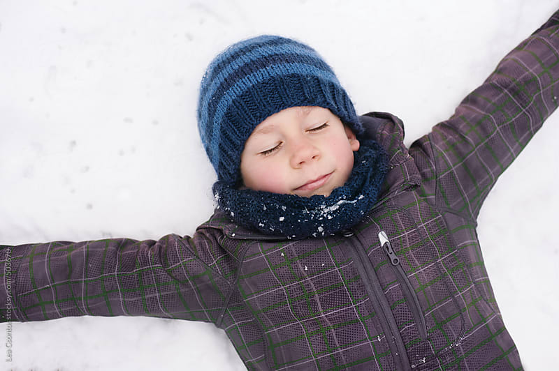 Boy lying on his back in the snow and daydreaming with closed eyes by Lea Csontos for Stocksy United