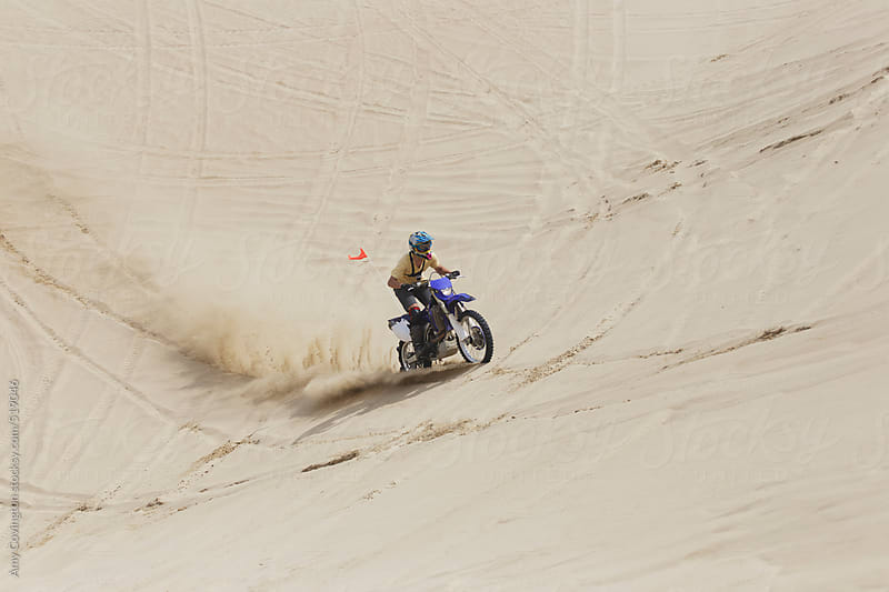 Young man riding a dirt bike up the sand dunes by Amy Covington for Stocksy United