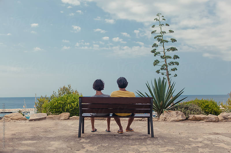 Father and son sitting on a bench overlooking the ocean on a summer day by Cindy Prins for Stocksy United