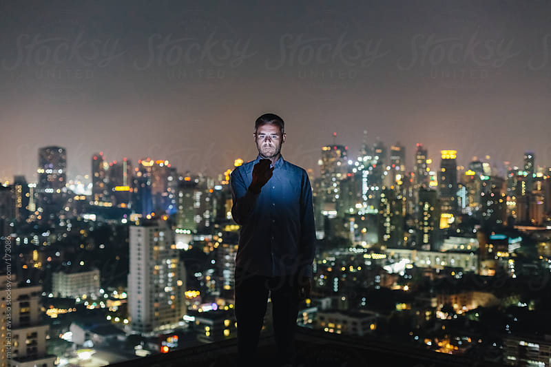 Man using his mobile phone on the roof over the cityscape by michela ravasio for Stocksy United