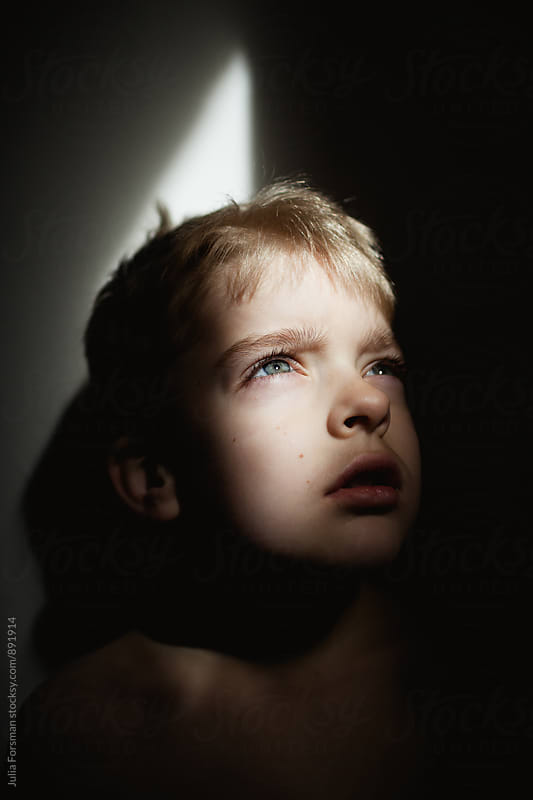 Portrait of child looking up into strong light with shadow around him. by Julia Forsman for Stocksy United
