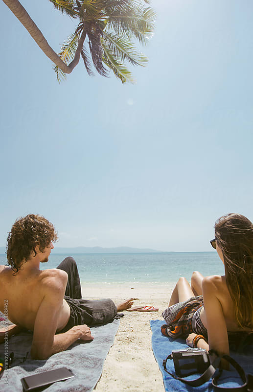 Enjoying the sun - couple sitting on the beach and looking at the ocean by Jovo Jovanovic for Stocksy United