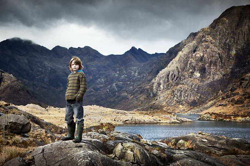 Young male standing in a dramatic landscape by James Ross for Stocksy United