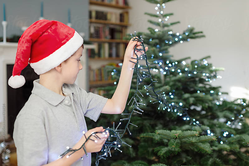 Child decorating his Christmas tree with lights by Rebecca Spencer for Stocksy United