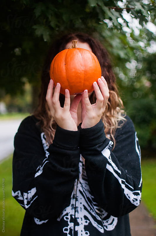 A young woman holding a pumpkin by Chelsea Victoria for Stocksy United