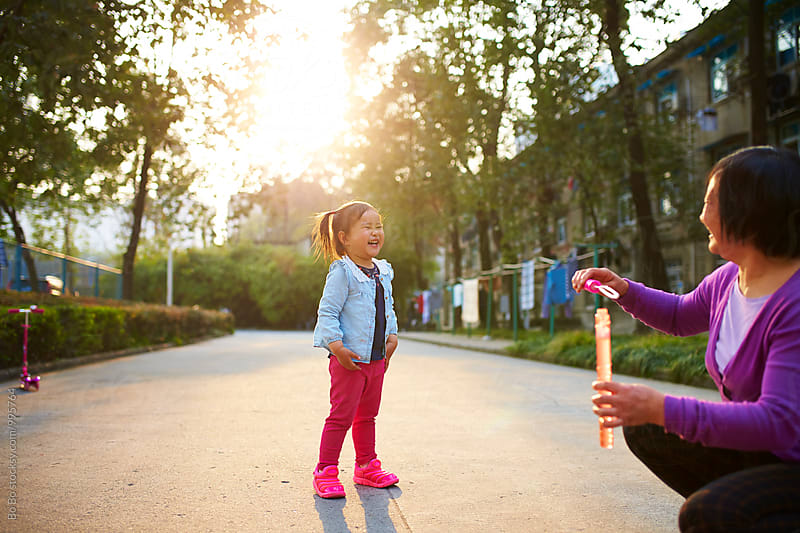 little asian girl playing with her grandmother outdoor by Bo Bo for Stocksy United