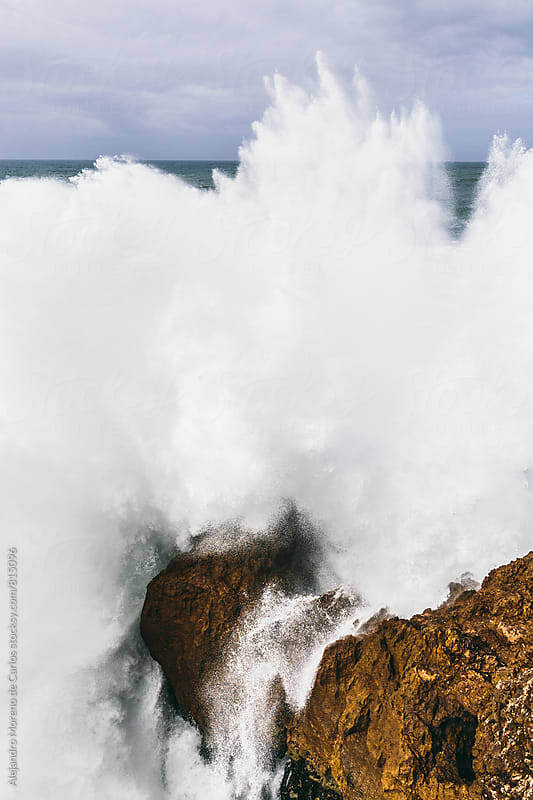Violent wave splash knocking on the rocks by Alejandro Moreno de Carlos for Stocksy United