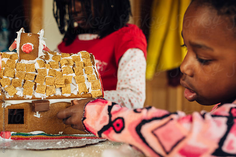 African American girl building a gingerbread house by Gabriel (Gabi) Bucataru for Stocksy United